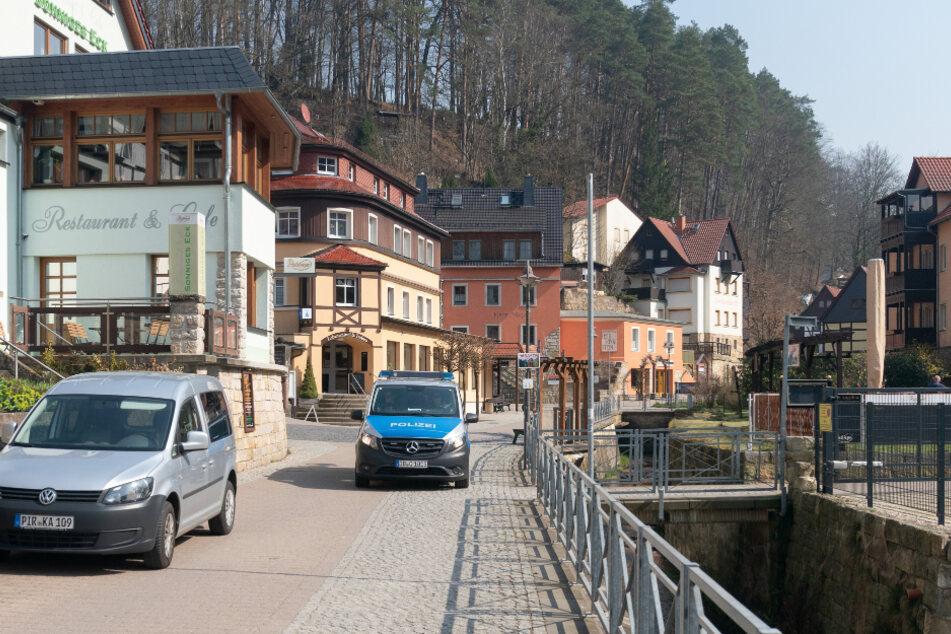Ein Polizeiauto fährt durch den fast menschenleeren Ort Rathen in der Sächsischen Schweiz, wo sonst Besucherströme unterwegs sind.