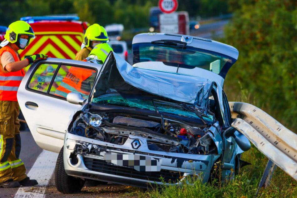 Bei einem schweren Verkehrsunfall ist ein Renault auf der A10 in die Leitplanke gekracht. Feuerwehrleute untersuchen das Wrack.