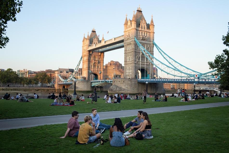 Zahlreiche Briten sitzen auf dem Rasen des Potters Fields Park vor der Tower Bridge.