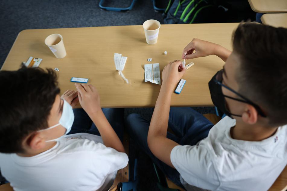 Zwei Schüler der Klasse 6a am Goethe-Gymnasium in Hamburg-Lurup machen einen Corona-Schnelltest im Klassenzimmer am ersten Schultag nach den Ferien. Das kindliche Immunsystem scheint jedoch auf die Attacken des Coronavirus besser vorbereitet zu sein als das von Erwachsenen.