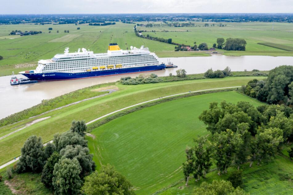 """Die Drohnen-Aufnahme zeigt das Kreuzfahrtschiff """"Spirit of Adventure"""" auf der Ems. Es wird von zwei Schleppern rückwärts in Richtung Nordsee gezogen."""