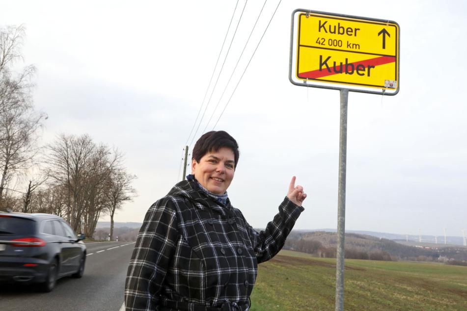Annett Richter (48) lacht über das Ortschild, das auch darauf hinweist, dass es noch 42.000 Kilometer sind, bis man nach einer Erdumrundung wieder in Kuber ist.