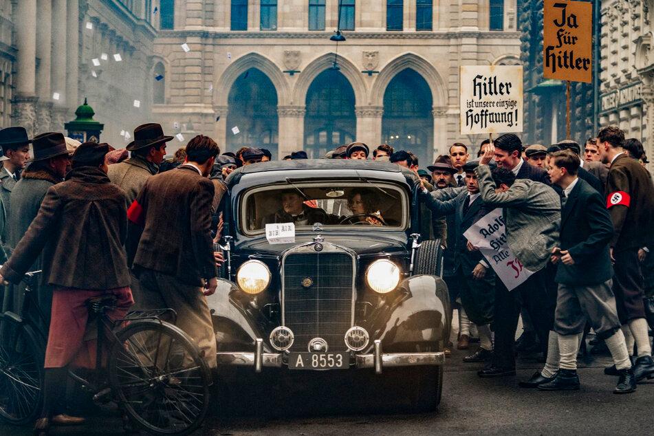 """""""Hitler ist unsere einzige Hoffnung"""": Kurz vor der Machtergreifung stoppen Nazi-Demonstranten in Wien den Wagen von Dr. Josef Bartok (Oliver Masucci, 52) und seiner Frau Anna (Birgit Minichmayr, 44)."""