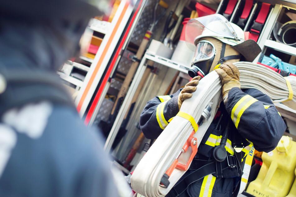 Mehr als 24 Stunden nach Ausbruch eines Brandes in einem Haus sind Feuerwehrleute noch mit Löscharbeiten beschäftigt. (Symbolbild)