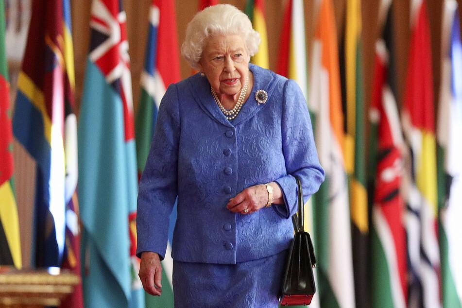 Die britische Königin Elizabeth II. geht im Rahmen des Commonwealth-Tages in der St. George's Hall auf Schloss Windsor an den Flaggen der Mitgliedsländer des Commonwealth vorbei.