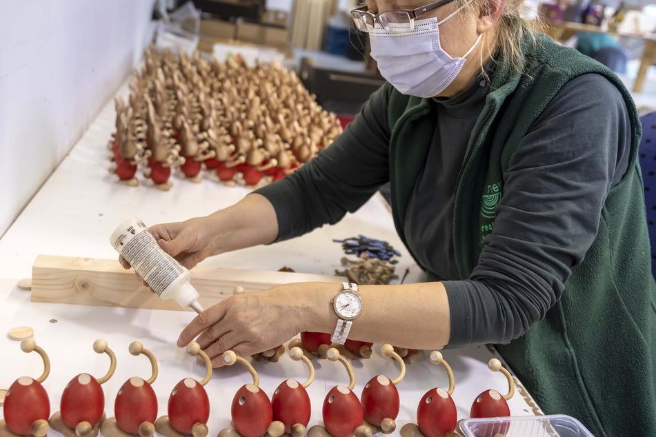 Mitarbeiterin Heike Bensch verleimt in der Werkstatt Figuren.