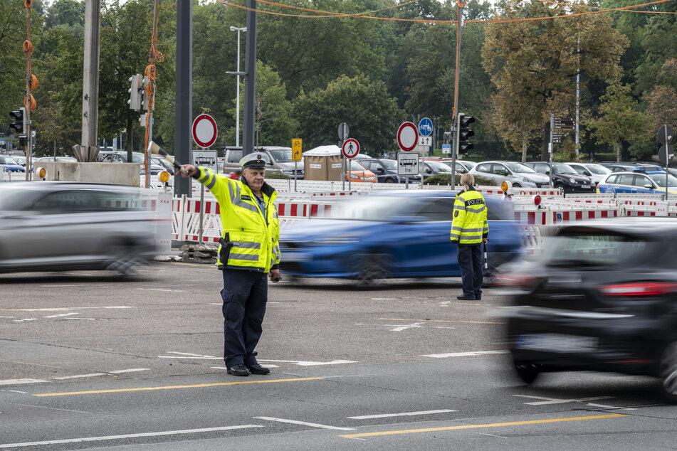 """Ein Polizeihauptmeister (56) und eine Polizeiobermeisterin (36) regeln mit """"Birkenzweigen"""" den Verkehr auf der smac-Kreuzung ohne Ampeln."""