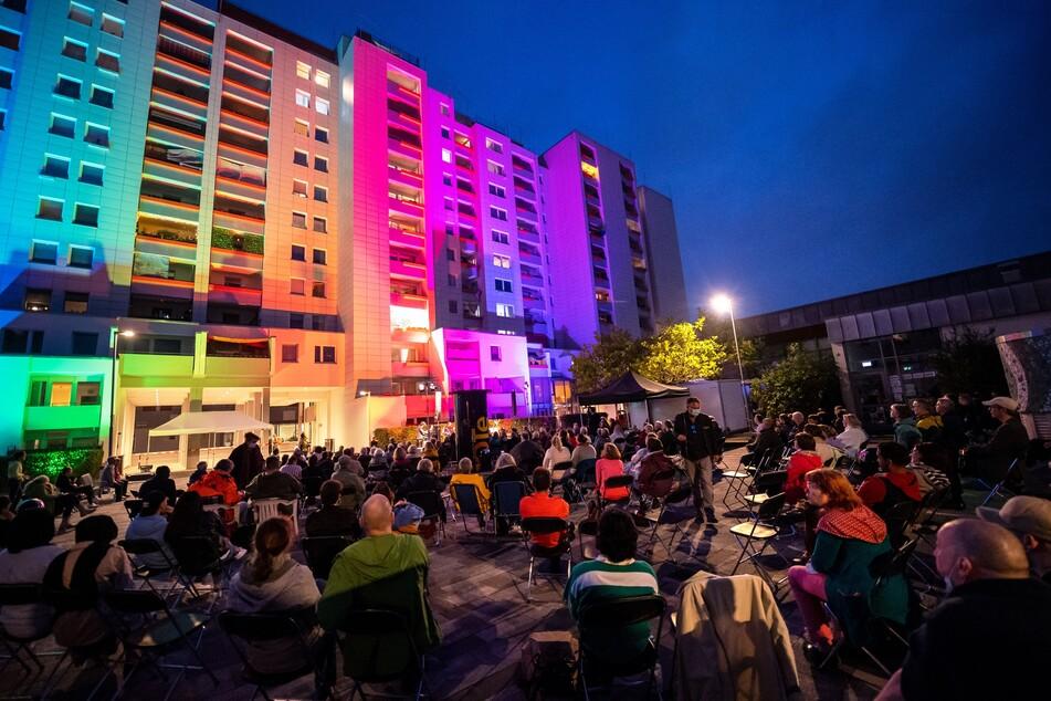 """Beim Freiluftkonzert """"Singende Balkone"""" konnten Zuschauer auf Sofas, Stühlen und Bänken Platz nehmen, um der Musik zu lauschen, Anwohnerinnen und Anwohner konnten auch von ihren Balkonen aus zusehen."""