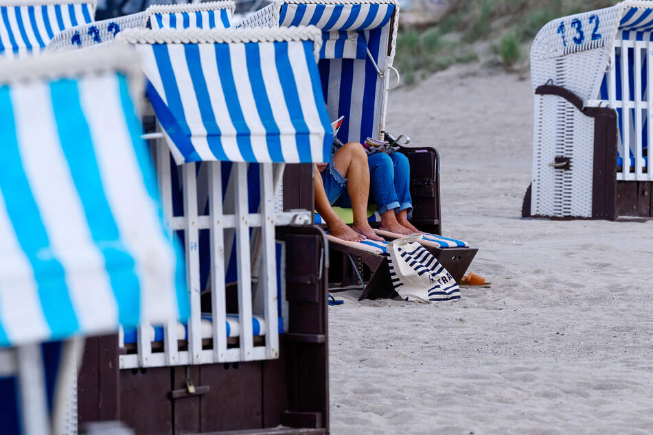 Am Strand sitzen Urlauber in einem Strandkorb.