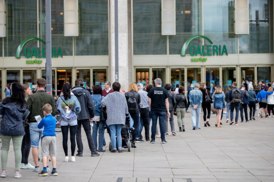 Menschen stehen auf dem Alexanderplatz in einer langen Schlange um bei Galeria Kaufhof einzukaufen.