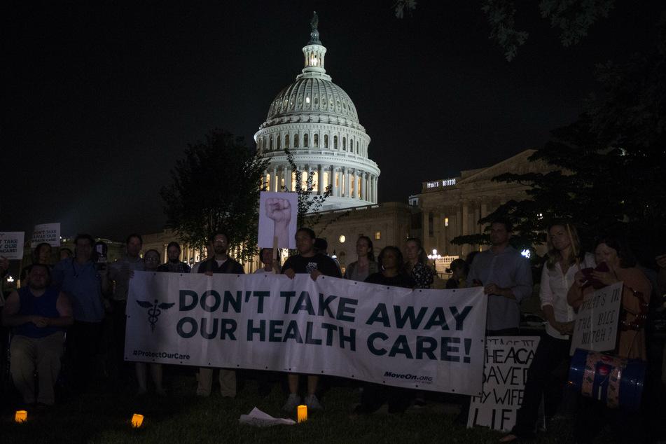 """Washington: Demonstranten halten vor dem Kapitol ein Banner mit der Aufschrift """"Don't take away our health care!"""" (Nehmt uns nicht unsere Krankenversicherung weg!) hoch."""
