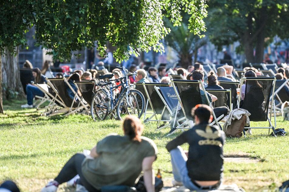 Menschen sitzen auf Liegestühlen und auf der Wiese. In Thüringen stecken sich aktuell vor allen jüngere Menschen mit dem Coronavirus an. (Symbolbild)