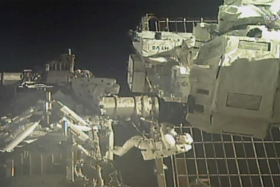 Christopher Cassidy (M,unten) und Robert Behnken (M,l,oben, abwärts blickend) arbeiten bei einem Außeneinsatz an der Internationalen Raumstation ISS. (Archivbild)