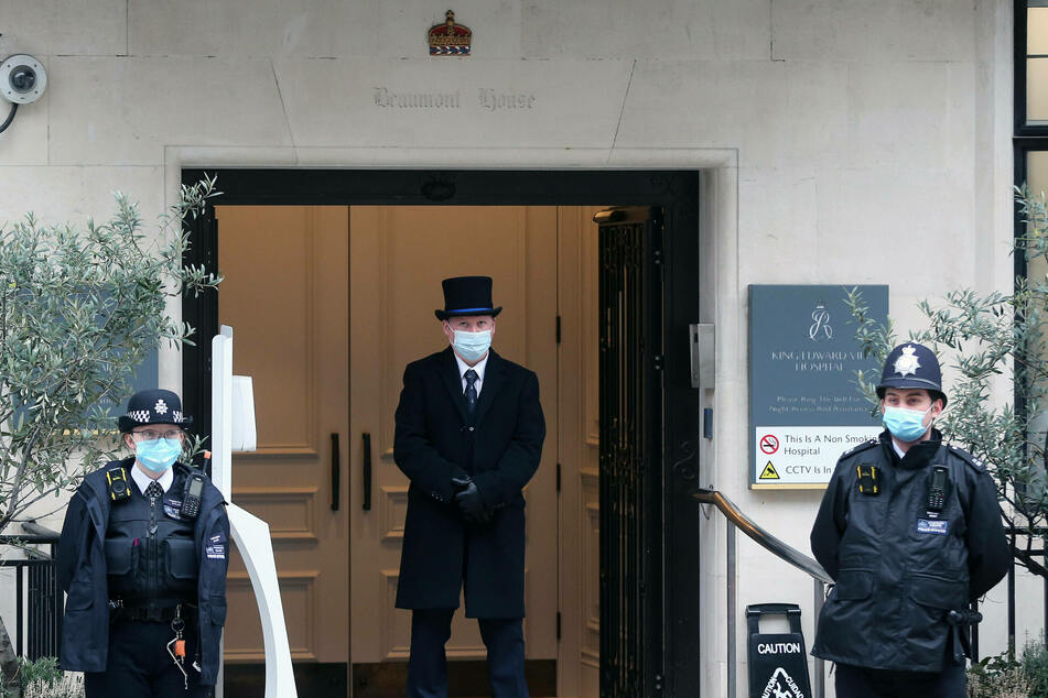 Police officers and a gatekeeper stand outside King Edward VII's Hospital where Britain's Prince Philip is being treated.