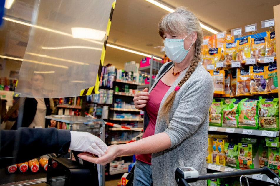 Ein Kundin bezahlt in einem Supermarkt in Berlin-Wilmersdorf, wobei sie einen Mund-Nasen-Schutz trägt.
