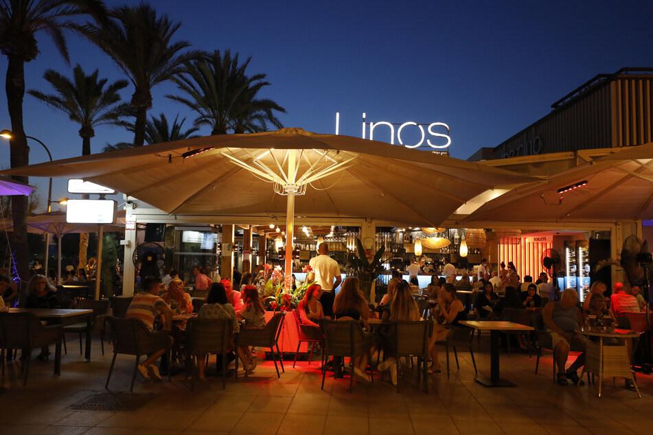 Menschen sitzen in einer Bar an der Strandpromenade von Palma. auf Mallorca sind die Corona-Zahlen wieder in die Höhe geschossen.