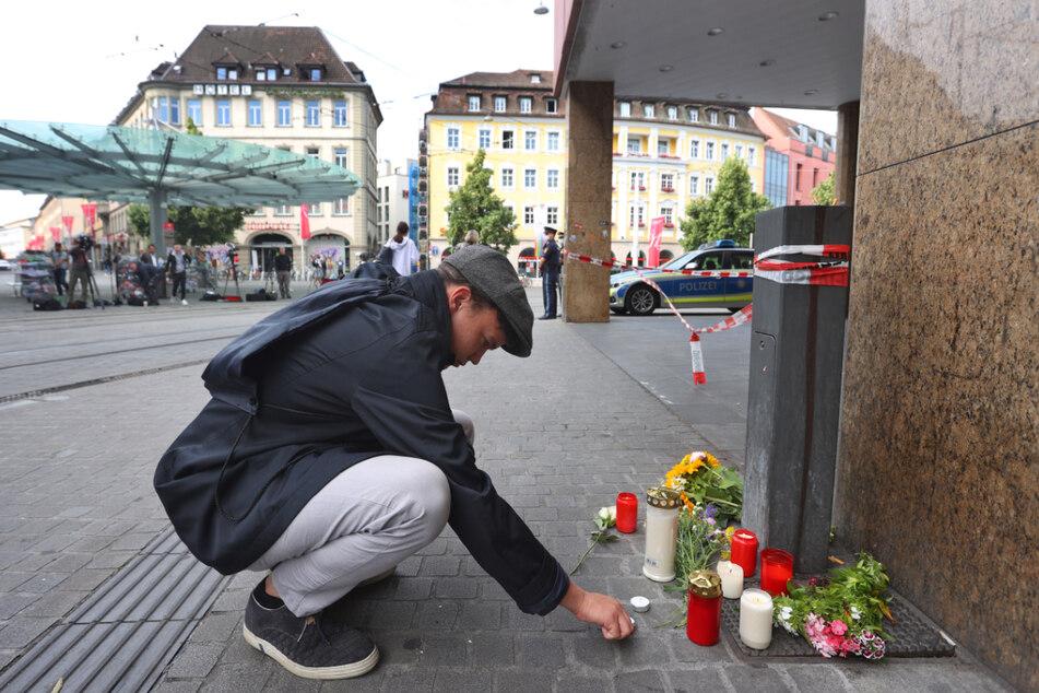 Würzburg, am Samstag: Ein junger Mann entzündet vor der Woolworth-Filiale am Barbarossaplatz eine Kerze.