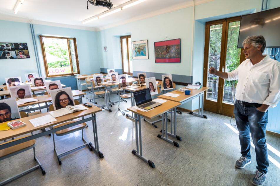 """Schweiz, Sion Sitten: Der Lehrer Christophe Blanc gibt per Videokamera in einem Klassenzimmer mit Bildern seiner Schüler in der Privatschule """"Ecole Ardevaz"""" Wirtschaftsunterricht. Die Schweiz beginnt rund sechs Wochen nach dem Schließen der meisten Geschäfte mit einer Lockerung der Corona-Schutzmaßnahmen."""