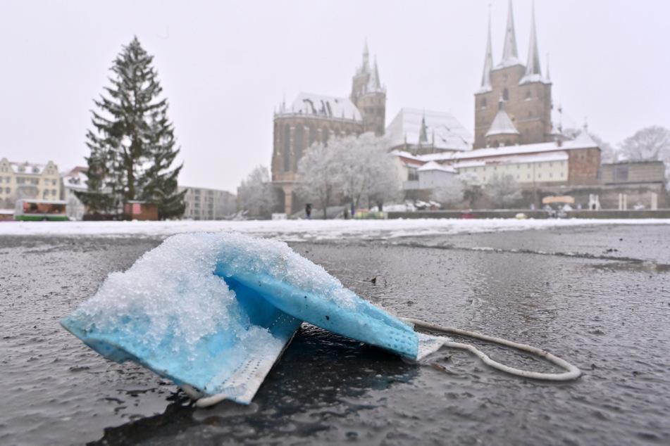 Eine gebrauchte Maske liegt im Schnee: In Thüringen sind die Corona-Fallzahlen weiter auf hohem Niveau. (Symbolbild)