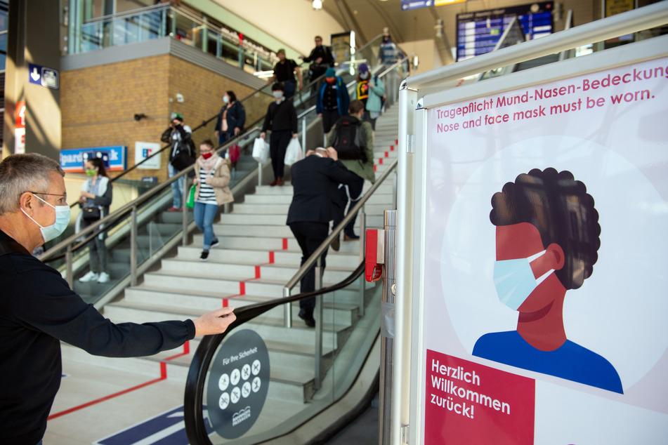 """Passanten mit Mundschutz gehen im Hauptbahnhof an einem Schild der Bahnhofs-Passagen mit der Aufschrift """"Herzlich willkommen zurück! Tragepflicht Mund-Nasen-Bedeckung."""" vorbei."""