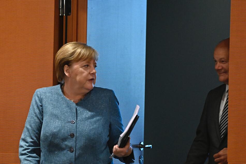 Bundeskanzlerin Angela Merkel (l, CDU) kommt neben Olaf Scholz (SPD), Bundesfinanzminister, zur Sitzung des Bundeskabinetts im Kanzleramt.