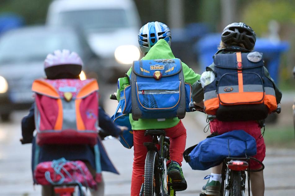 Kinder sind auf einer Straße mit dem Fahrrad unterwegs zur Schule.