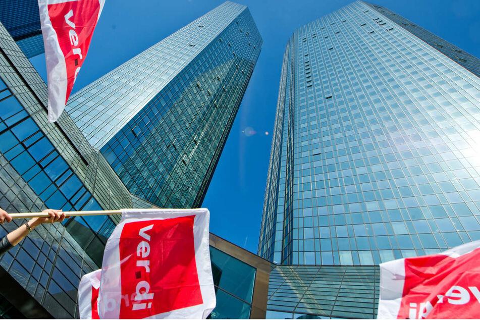 Verdi-Fahnen vor den Türmen der Deutschen Bank in Frankfurt am Main: Die Mitarbeiter mehrerer öffentlicher und privater Banken sind am Freitag zum Warnstreik aufgerufen. (Archivbild)