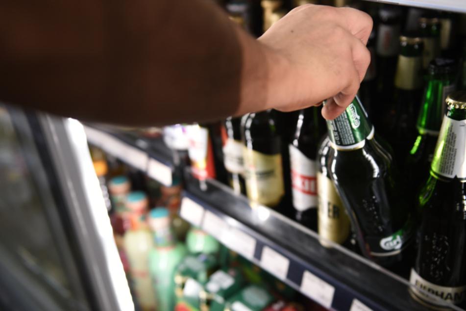 Ein Mann holt eine Flasche Bier aus einem Kühlschrank in einem Spätkauf.