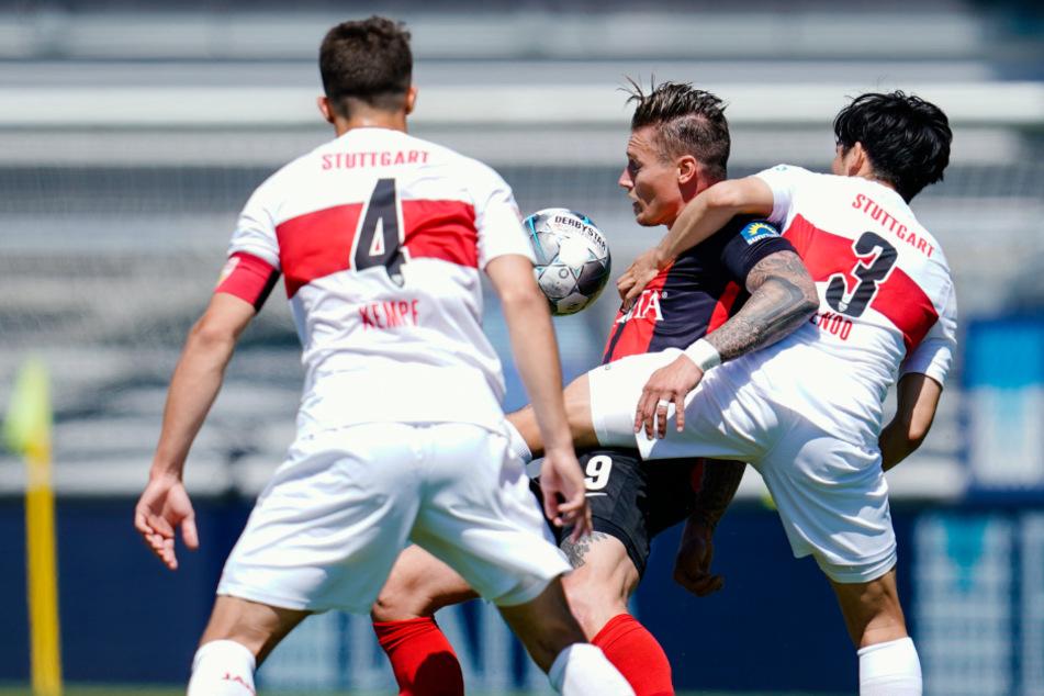 Stuttgarts Marc Oliver Kempf (l-r), Wiesbadens Manuel Schäffler und Stuttgarts Wataru Endo kämpfen um den Ball.