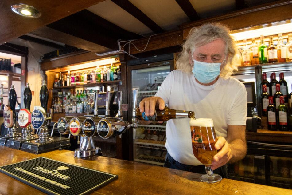 """Großbritannien: Phil Weaver, Besitzer des """"The Old Smithy Pub"""" in Church Lawford, Rugby, trägt einen Mund-Nasen-Schutz, während er Bier einschenkt."""