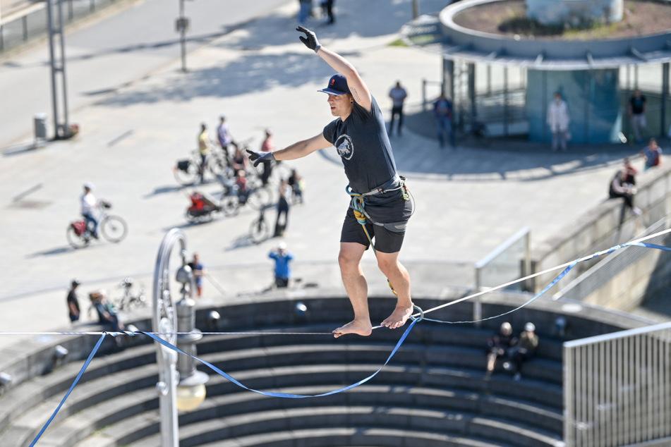 Peter Bessler balanciert über dem Theaterplatz in Chemnitz in rund 20 Metern Höhe über eine Slackline bei einer Werbeaktion für das Slackfest.
