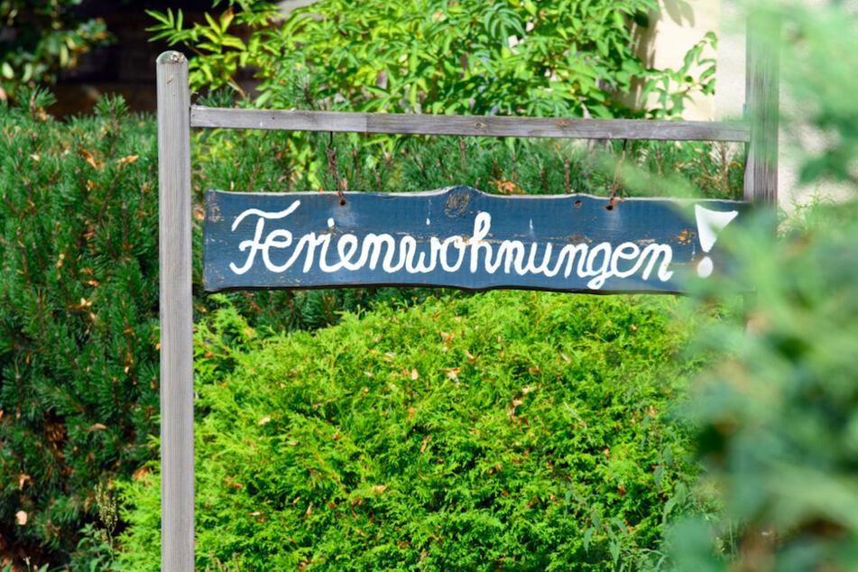 """Ein Schild """"Ferienwohnungen!"""" steht vor einem Haus zwischen Bäumen und Sträuchern."""