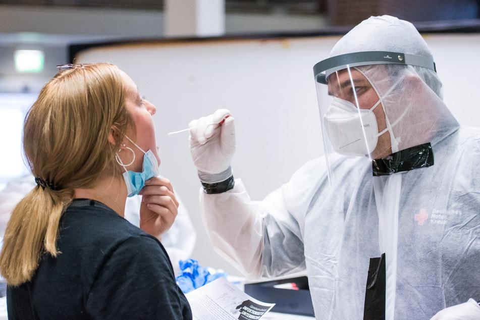 Eine Reisende lässt am Flughafen von einem Mitarbeiter des Deutschen Roten Kreuzes (DRK) einen Corona-Test machen.