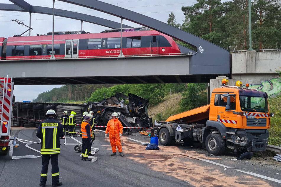 Die Zugmaschine des Schilderwagens ist durch den Zusammenprall herumgeschleudert worden und entgegengesetzt der Fahrtrichtung zum Stehen gekommen. Dahinter liegt das Lkw-Wrack unmittelbar unter einer Eisenbahnbrücke.