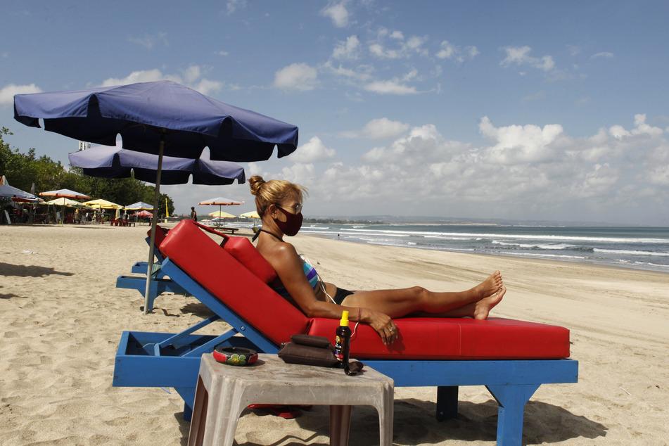 Bali: Eine Touristin trägt beim Sonnen am Strand einen Mund-Nasenschutz.