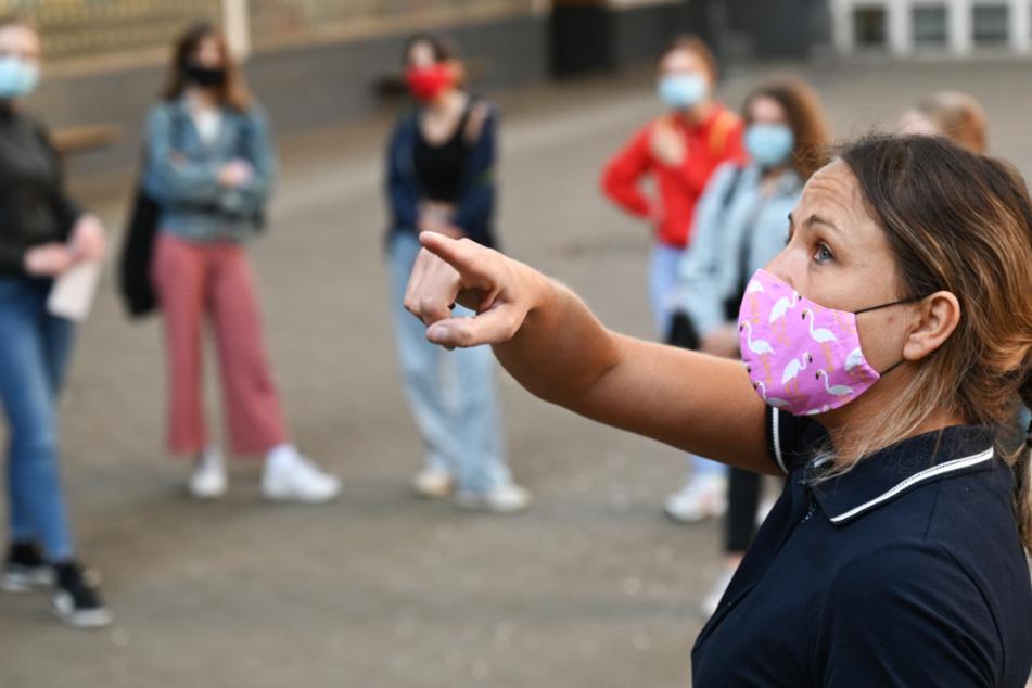 Eine Lehrerin und Schüler eines Deutsch-Kurses stehen mit Schutzmasken auf dem Schulhof eines Frankfurter Gymnasiums.