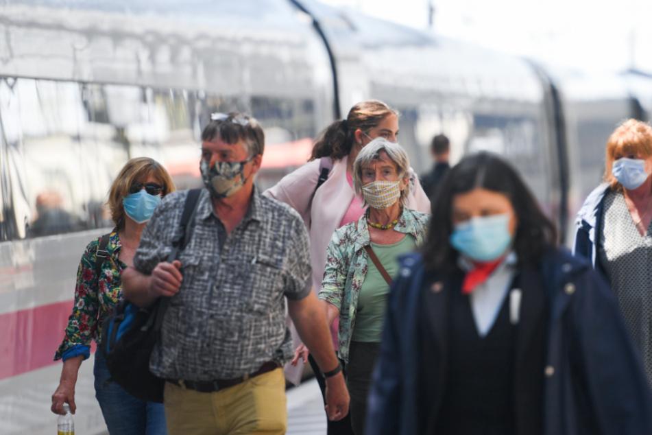 Mit Mundschutz bekleidete Passagiere steigen aus einem Zug aus. (Symbolbild)
