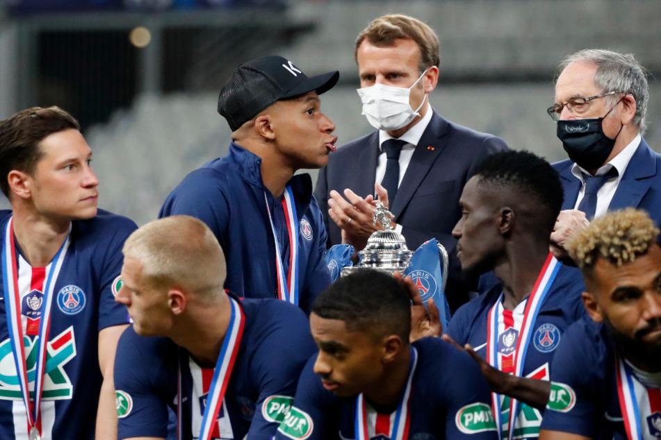 Pokal Frankreich, Paris Saint-Germain - AS St. Étienne, Finale: Emmanuel Macron (M) applaudiert, während Kylian Mbappe (3.v.l.) von der PSG an der Trophäe vorbei läuft.
