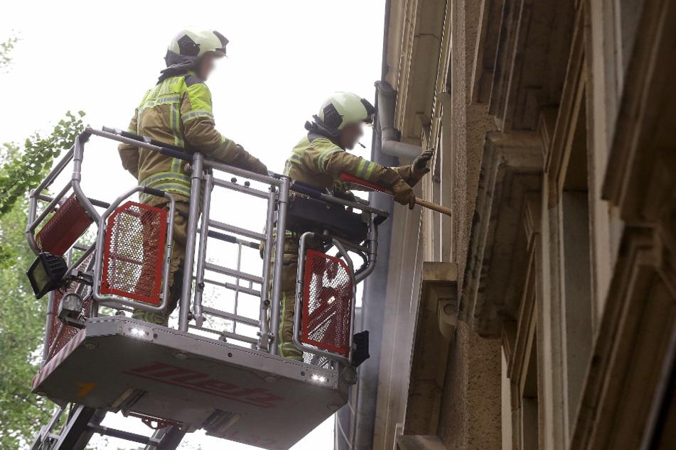 Zwei Feuerwehrmänner vor einem Fenster im zweiten Stock.