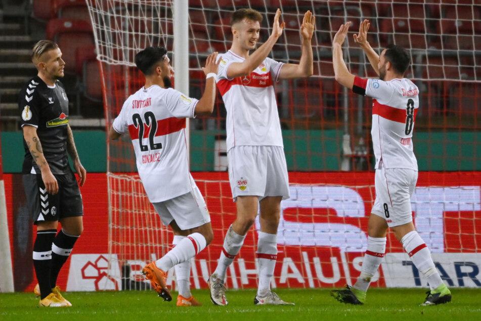 Die VfB-Profis Nicolas Gonzalez (l., 22) und Gonzalo Castro (r., 33) jubeln Sasa Kalajdzic (23, Mitte) zu, der gegen den SC Freiburg das entscheidende Tor zum Achtelfinaleinzug schoss.