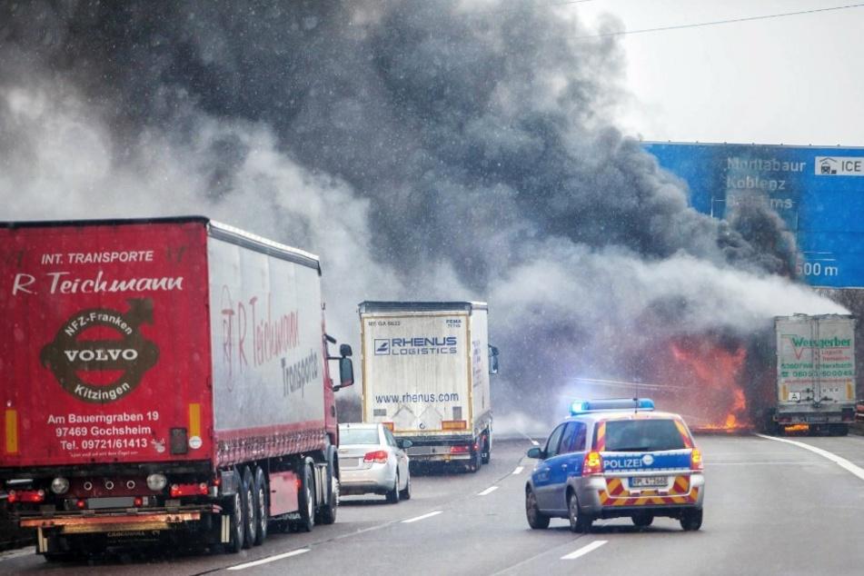 ein LKW auf der Autobahn A3 brennt. während sich nachfolgende Fahrzeuge dem brennenden Lastwagen nähern regelt ein Streifenwagen den Verkehr. Alles ist in dichten Rauch gehüllt.