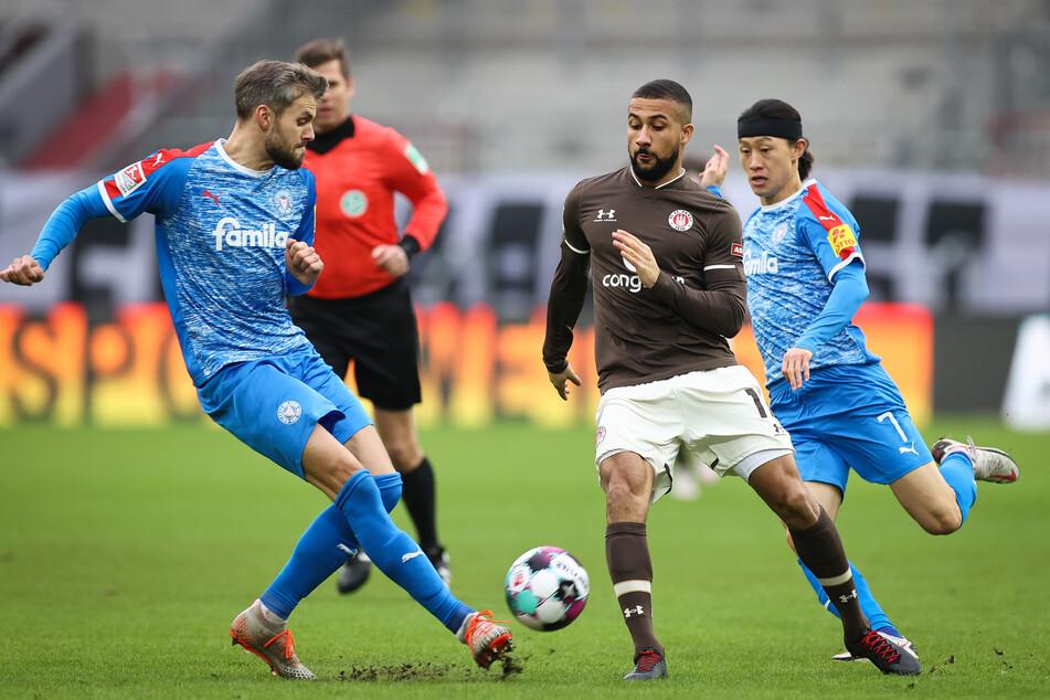 Daniel-Kofi Kyereh (M., hier im Zweikampf mit Holstein Kiels Stefan Thesker (l.) und Jae-sung Lee) bereitete das Tor von Marmoush vor.