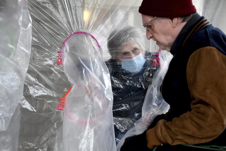 """Louisville, USA: Lynda Hartman (75) besucht ihren 77-jährigen Ehemann Len Hartman, der an Demenz leidet, in einem """"Umarmungszelt"""", das die Verbreitung des Coronavirus verhindern soll."""