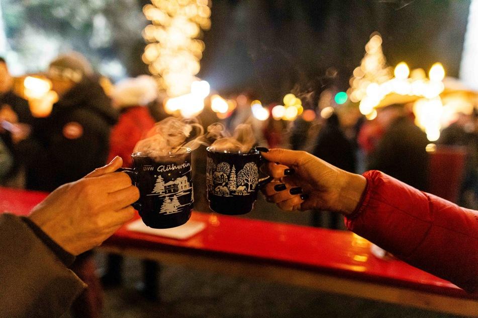 Zwei Besucherinnen stoßen auf dem Weihnachtsmarkt mit Glühwein an.