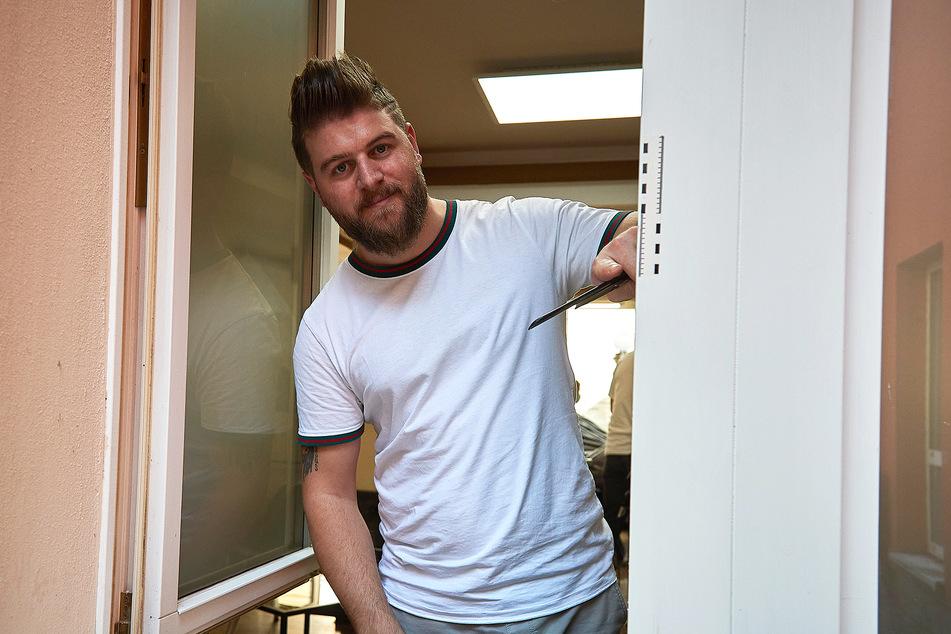 Friseurmeister Rostom Elai (30) zeigt, wo die Einbrecher in den Laden kamen.