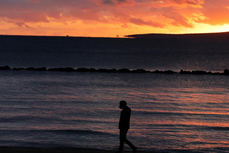 Ein Mann mit Gesichtsmaske spaziert während des Sonnenuntergangs am Strand von Palma entlang.
