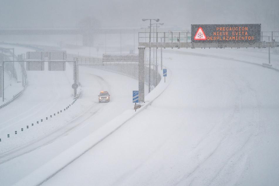 Ein Rettungsfahrzeug fährt auf der leeren, schneebedeckten Schnellstraße M-30 in Madrid.