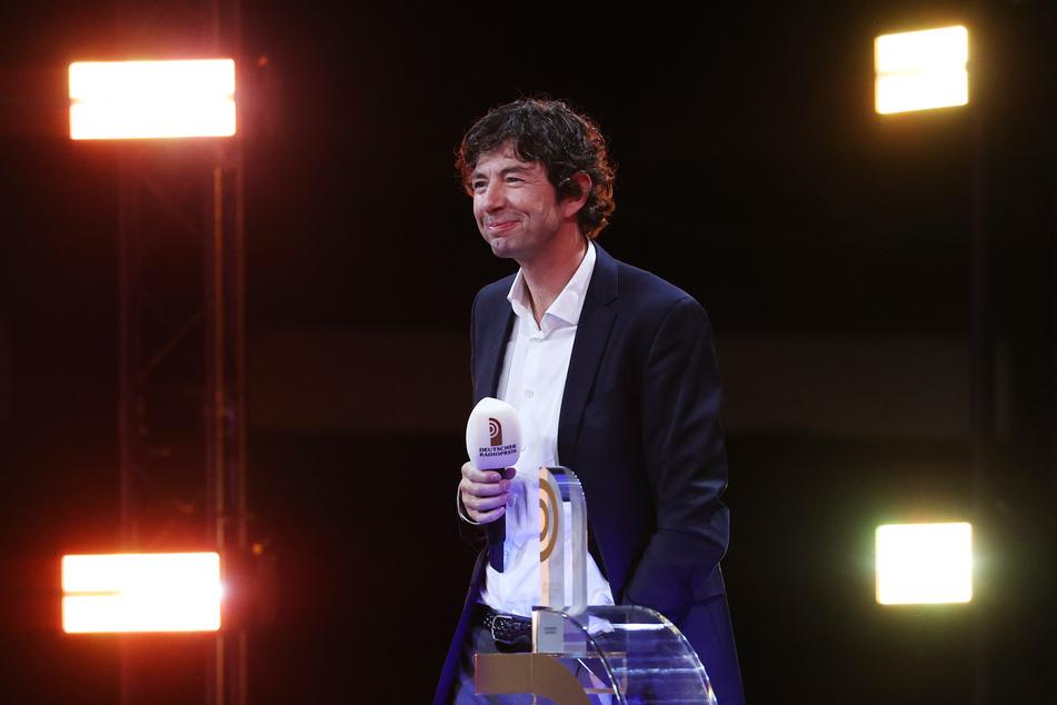 Christian Drosten (48) steht während der Verleihung des 11. Deutschen Radiopreises auf der Bühne neben seinem Sonderpreis des Beirates.