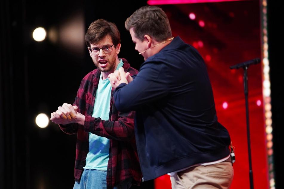 """Chris Tall (29, r) erlernt von """"Supertalent"""" Guy First (28) das Furzen mit den Händen."""