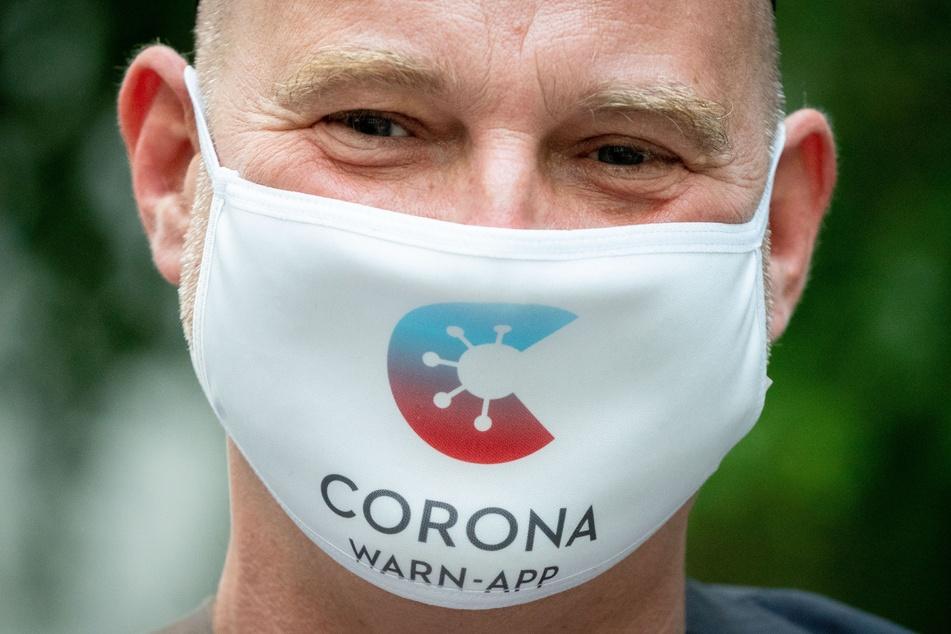 Rainer Knirsch, Telekom-Pressesprecher, trägt zu Beginn einer Pressekonferenz zu 100 Tage Corona-Warn-App einen Mund-Nasen-Schutz mit dem Logo der App im Haus der Bundespressekonferenz.